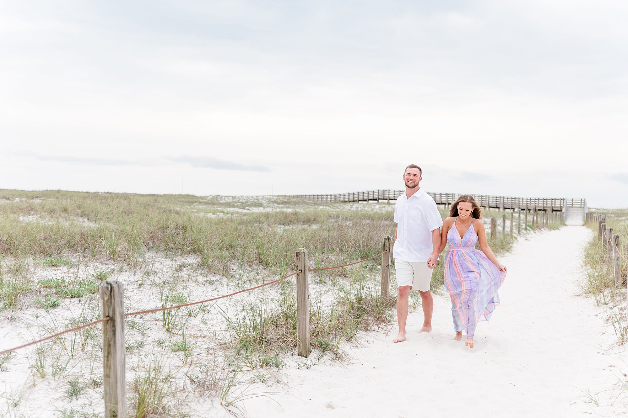 Bride and Groom walking along a beach path at the beach engagement session in Orange Beach, Alabama