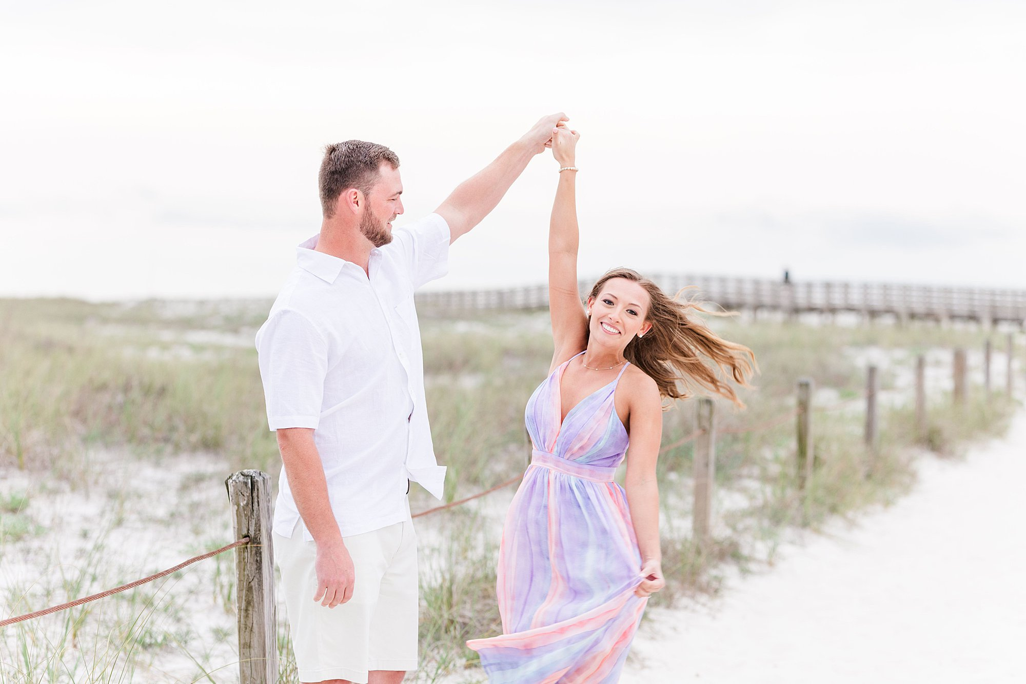 Groom twirling his bride on the beach walkway at their beach engagement session in Orange Beach, Alabama