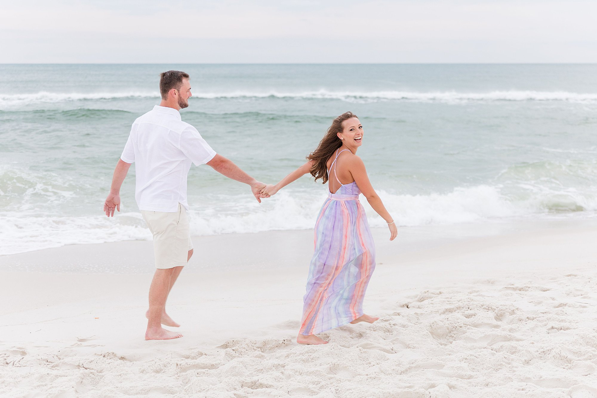 Bride leading her groom along the beach at their engagement session in Orange Beach, Alabama