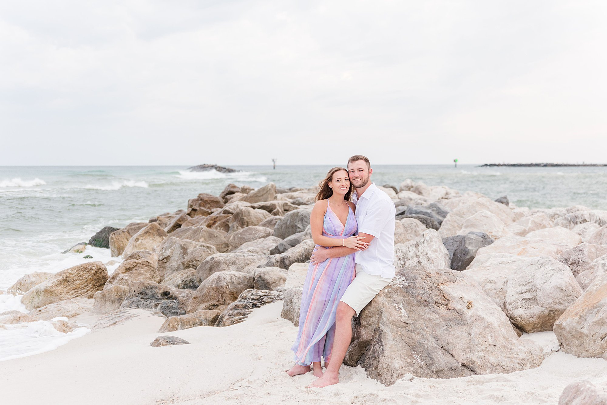Bride and Groom snuggling on the jetty at Alabama Point at their beach Bride leading her groom along the beach at their engagement session in Orange Beach, Alabama