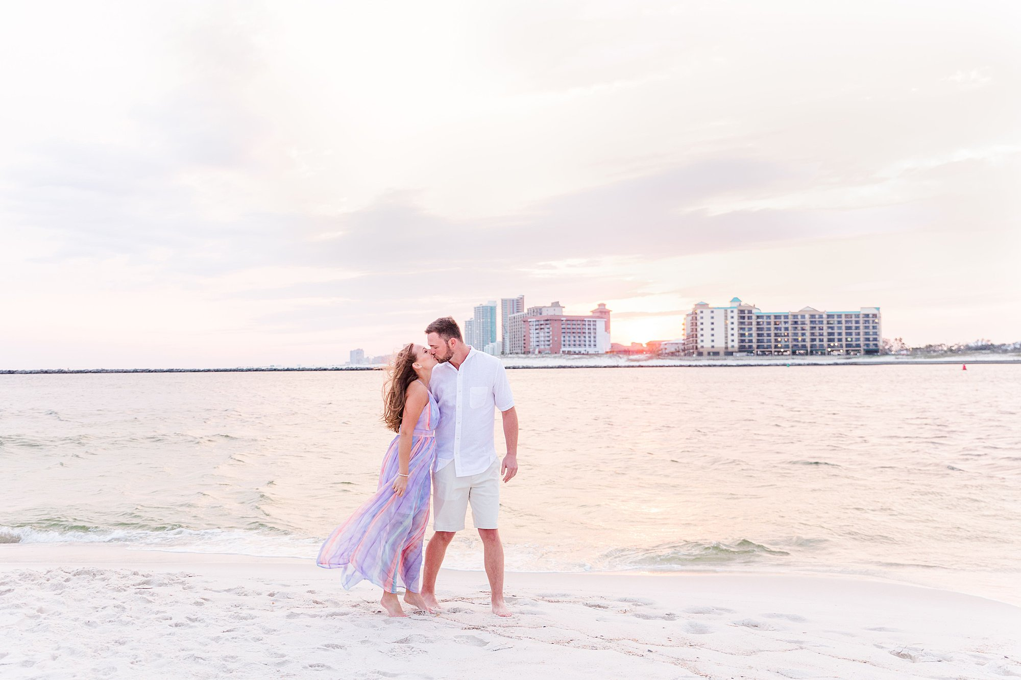 Bride and Groom walking along the beach with a stunning sunset at their beach Bride leading her groom along the beach at their engagement session in Orange Beach, Alabama