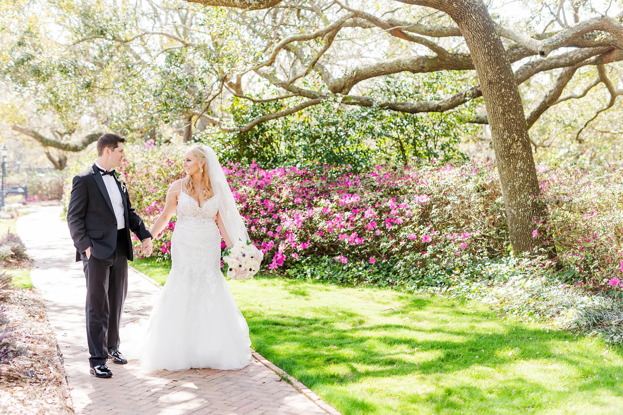 bride and groom walk through gardens in Alabama