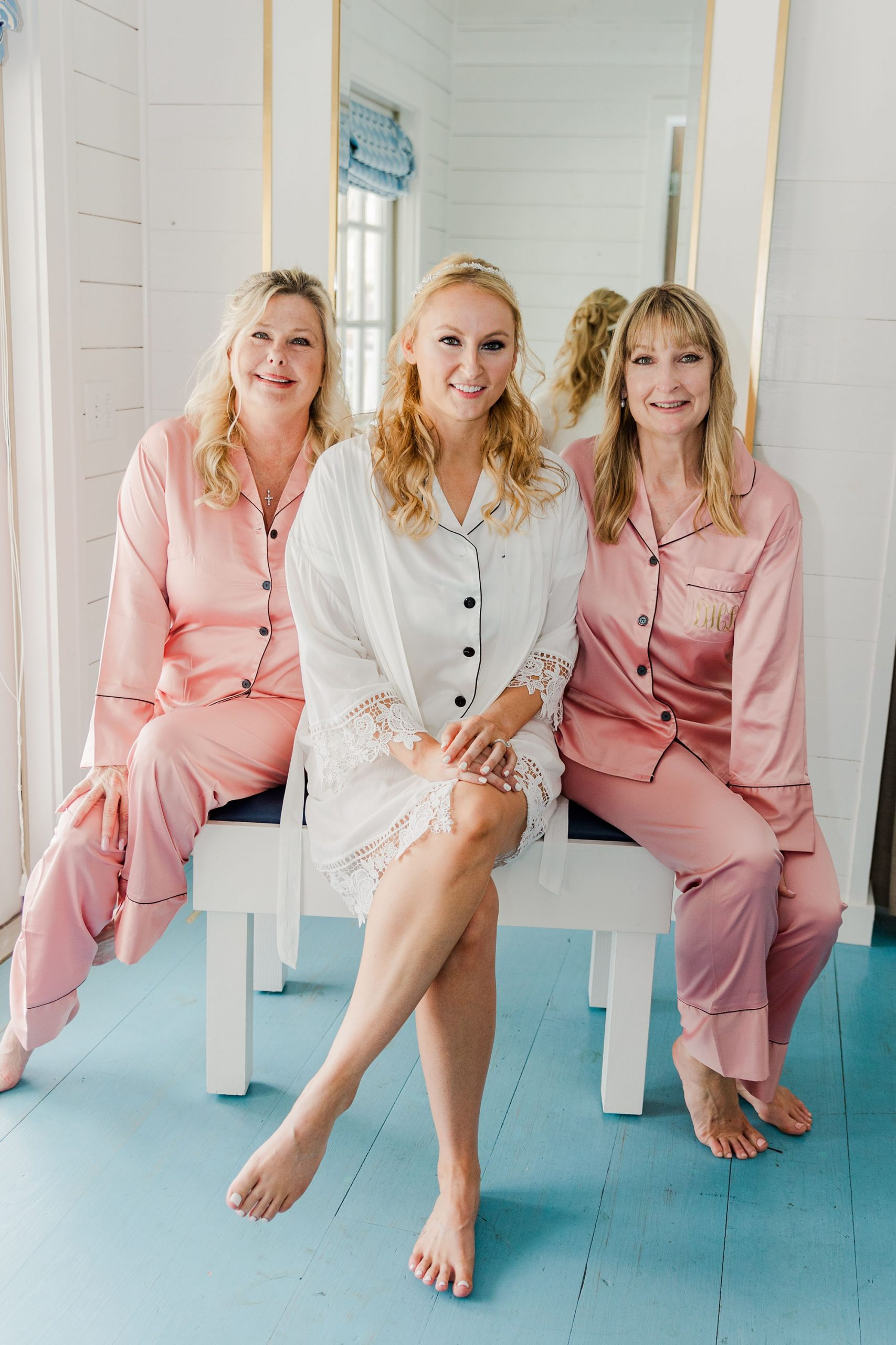 bride sits on bench with bridesmaids in pink robes