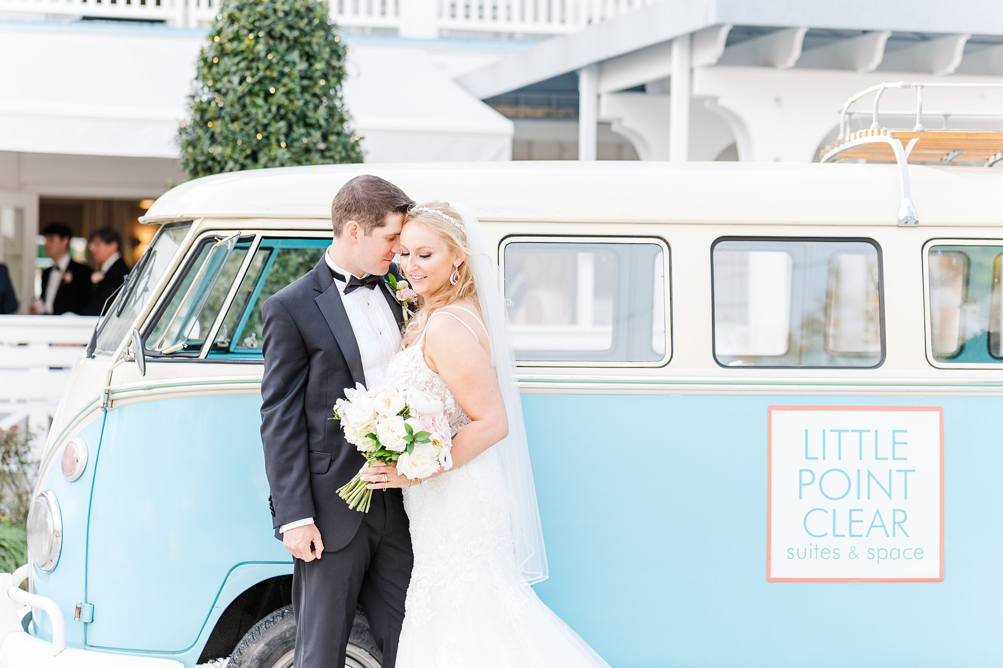 bride and groom pose next to light blue bus at Little Point Clear