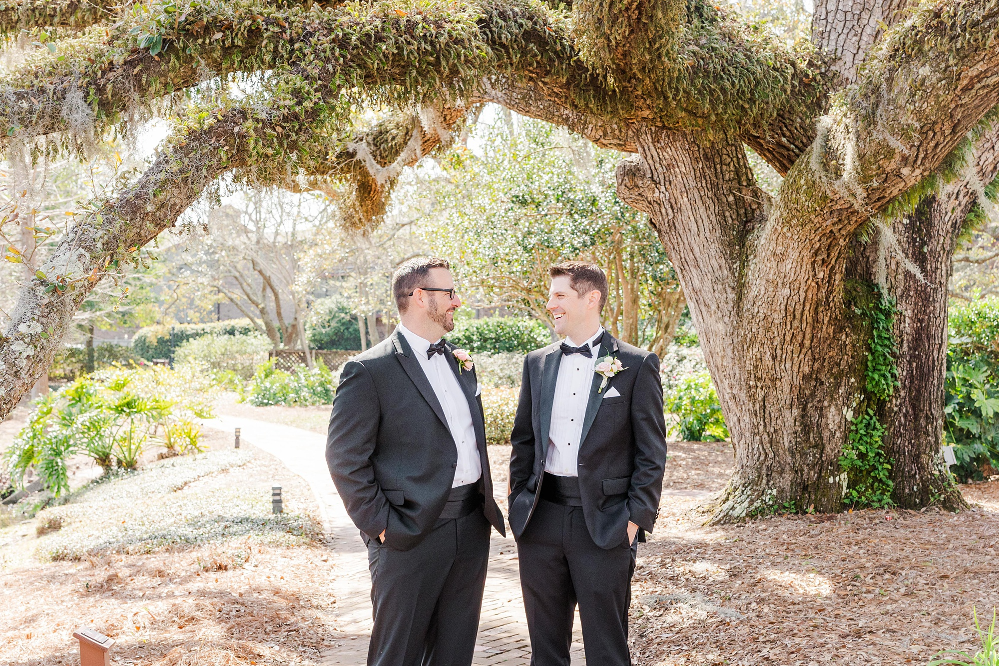 groom and groomsman laugh under tree