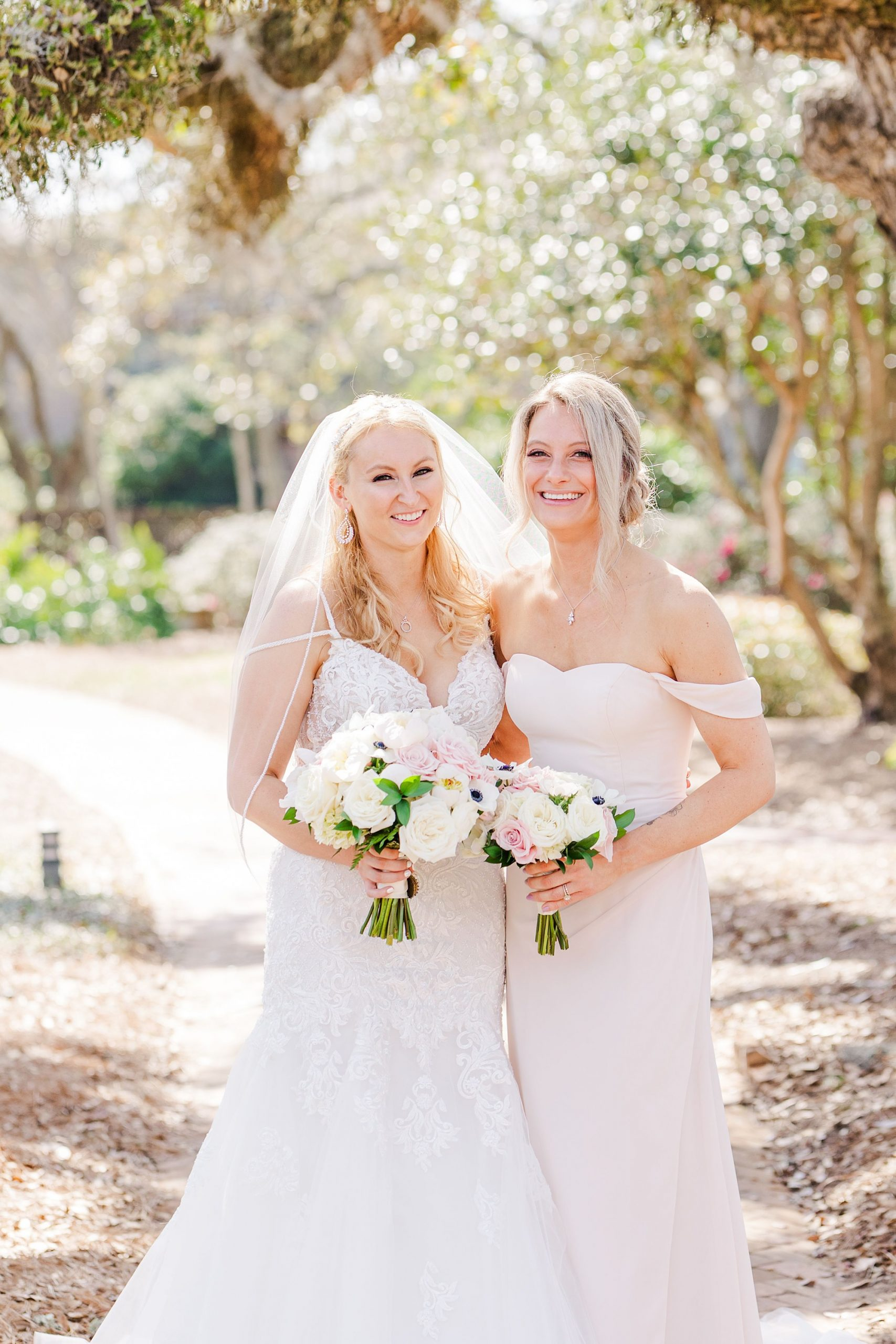 bride and bridesmaid in pink dress pose together in Fairhope AL