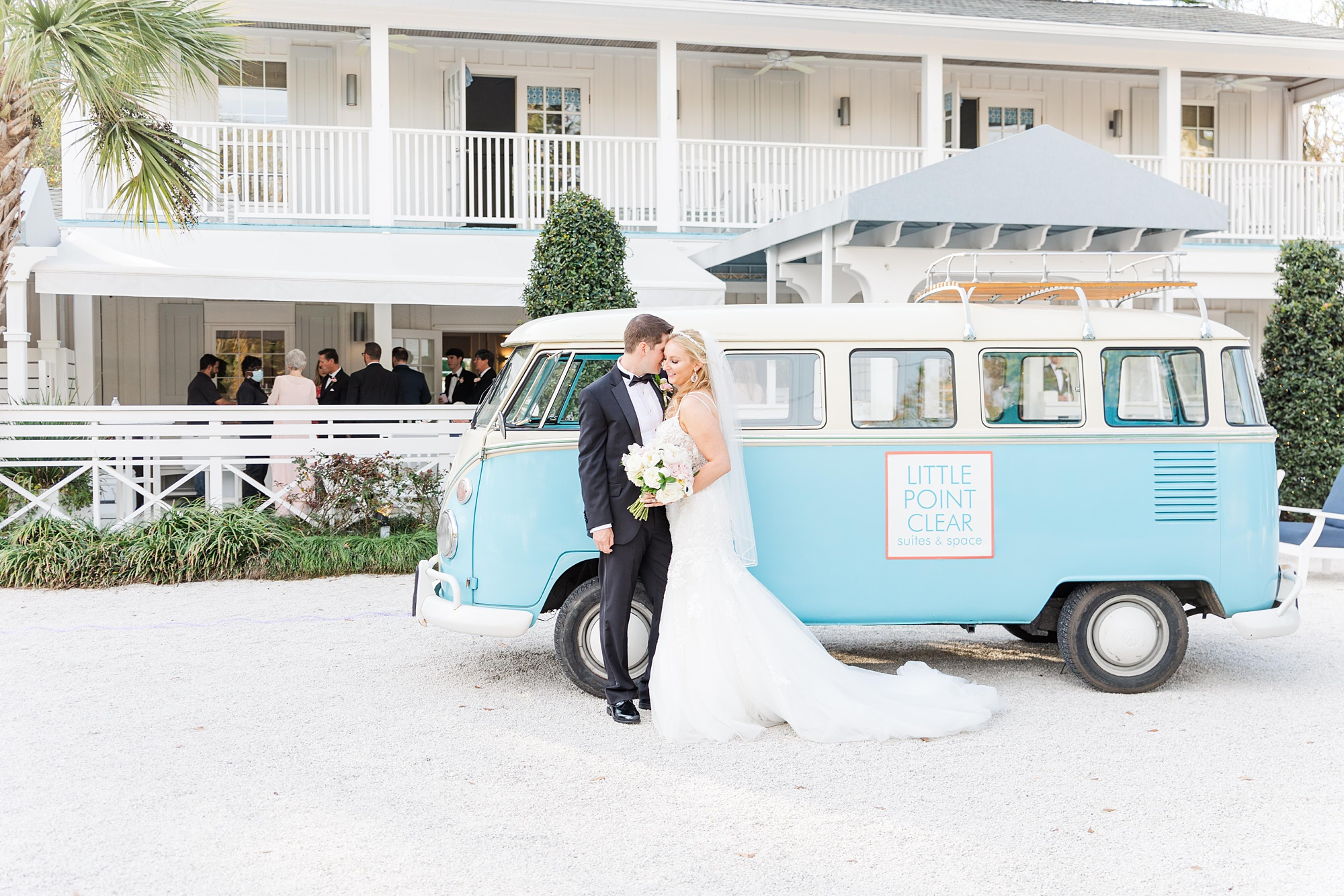newlyweds pose by VW bus at Little Point Clear