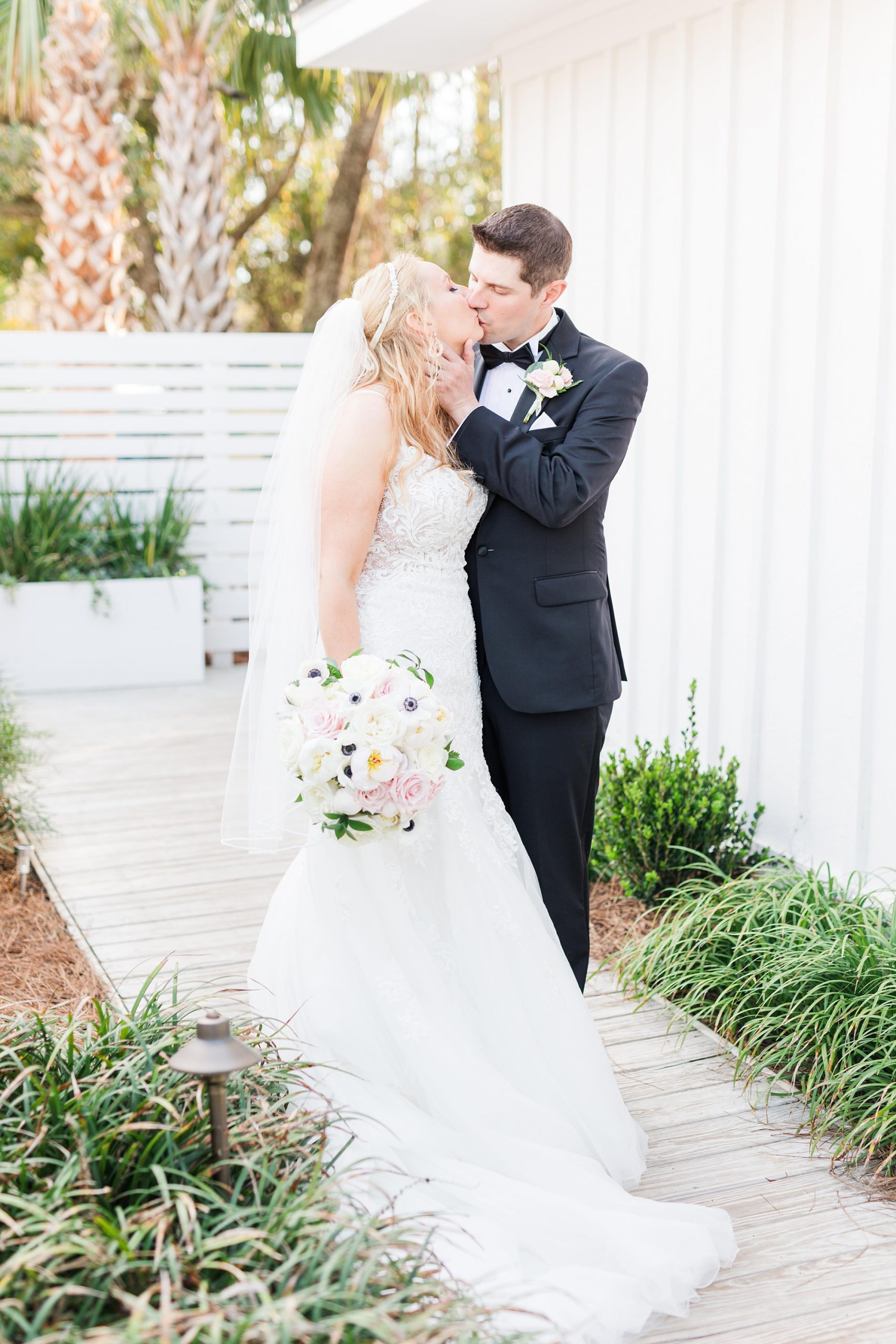 bride and groom kiss by white wall at Little Point Clear