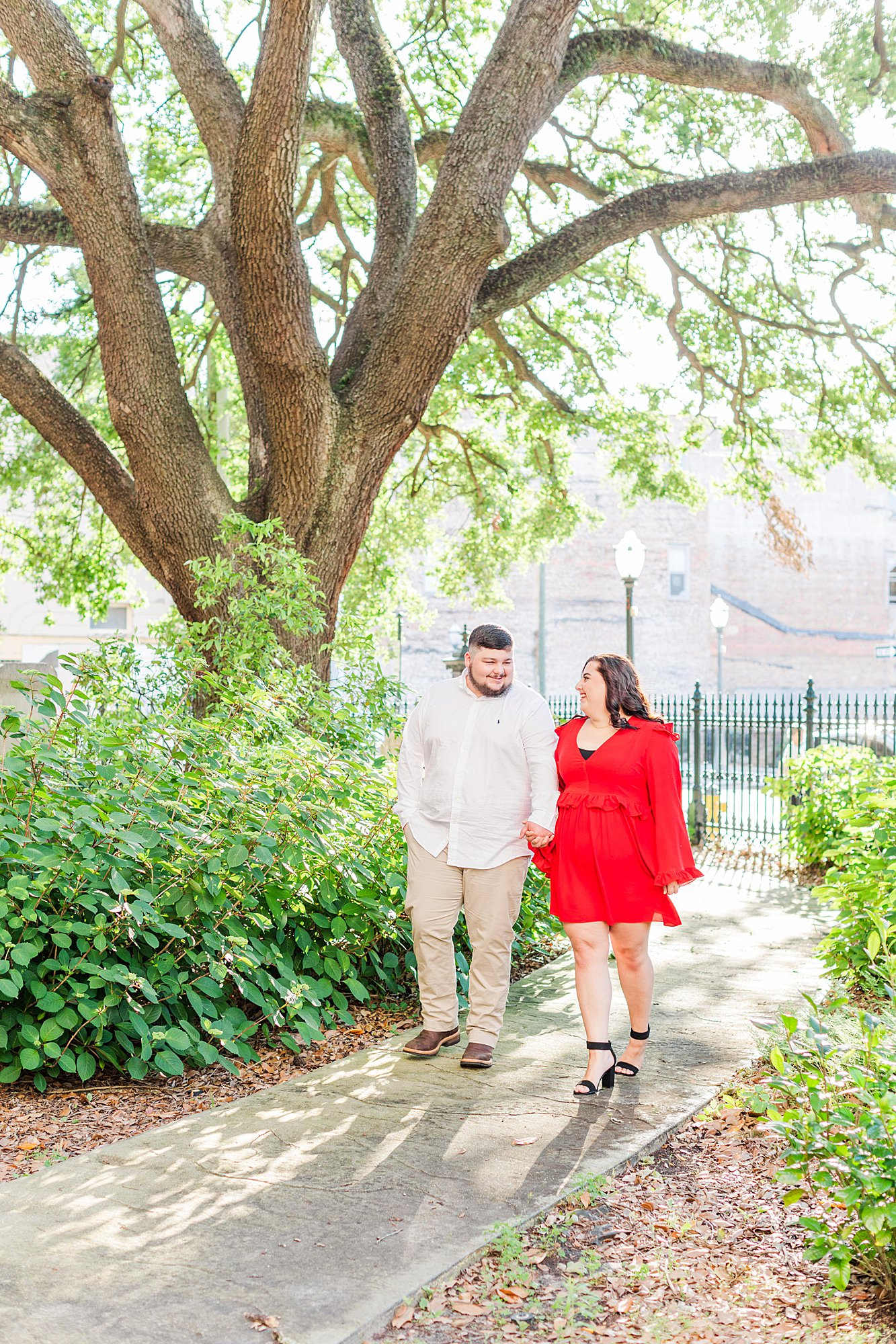 Engaged couple walking at their engagement session in downtown Mobile, AL