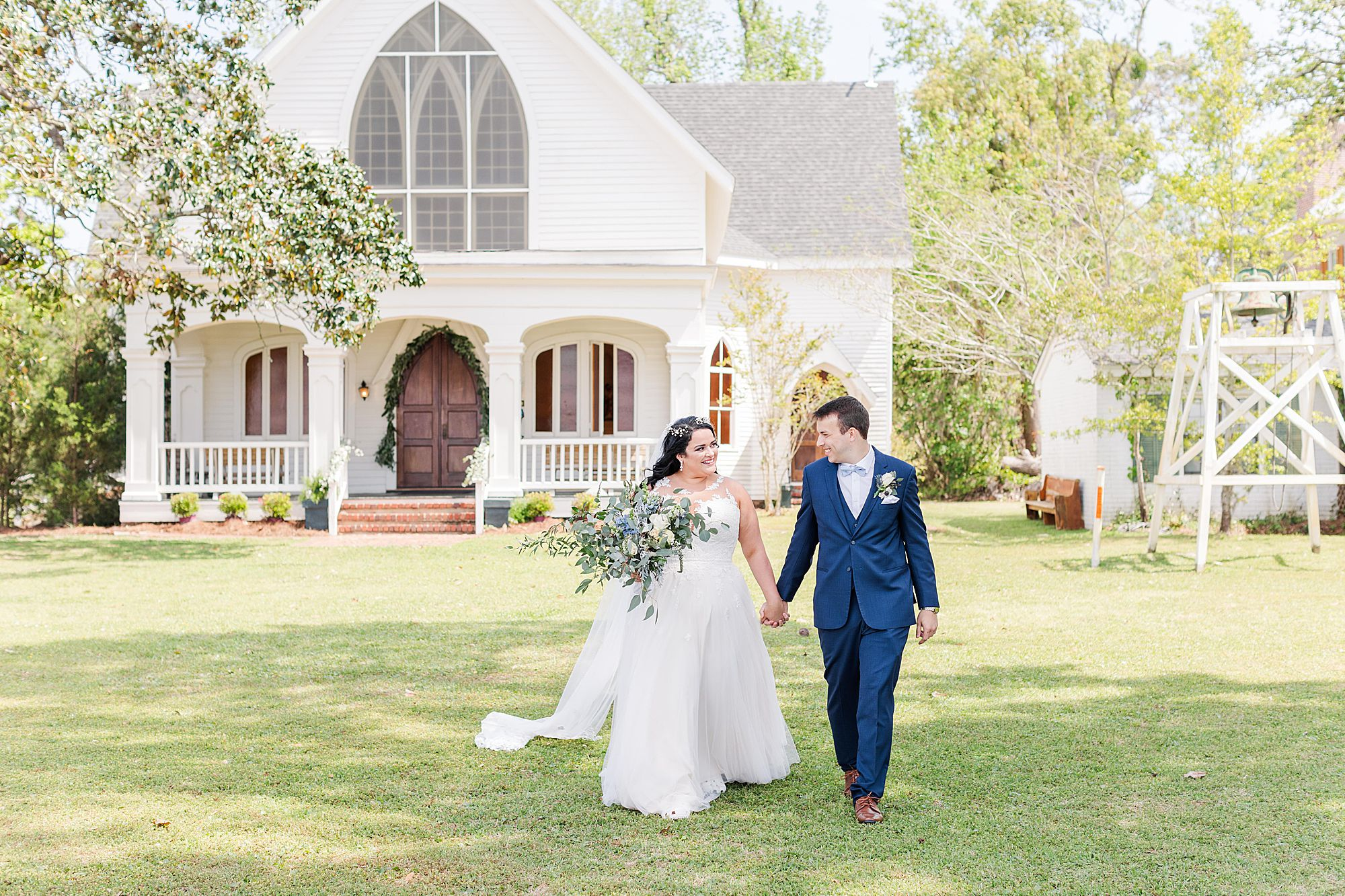 bride and groom walk in front of church