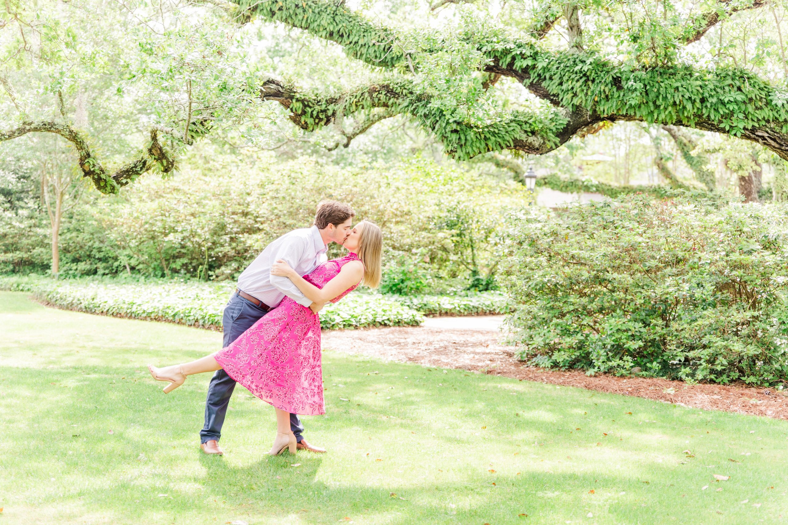 An Engaged Couple kissing under a live oak at the Grand Hotel in Point Clear, Alabama photographed by Goodie and Smith Weddings