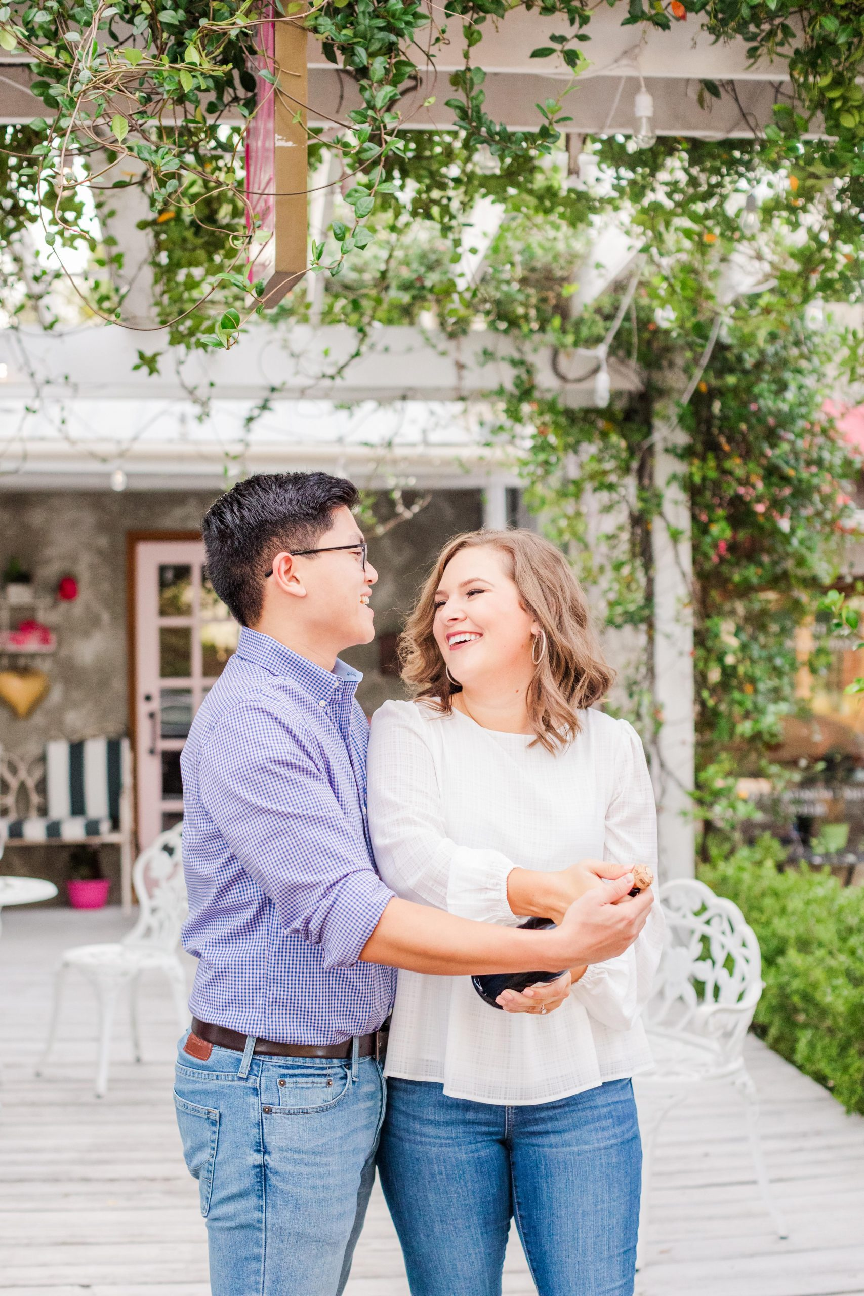 Couple toasting with champagne at their Downtown Fairhope Engagement Session